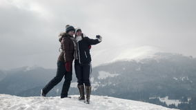Two girlfriends do selfie at mountain top stock footage