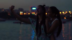 Two girlfriends do selfie at night on a background of lights. slow motion. Two girlfriends do selfie using the phone on a background of night lights in the city stock video