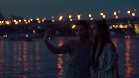 Two girlfriends do selfie at night by the river against the backdrop of lights. slow motion. Two girlfriends do selfie using the phone near the river against a stock video