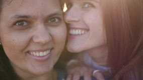 Two girlfriends do selfie on the phone, smile, pose. SLOW MOTION. HD, 1920x1080. stock footage