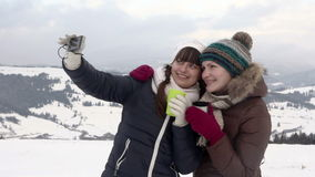Two girlfriends does selfie in the winter. Two girlfriends does selfie at the top of mountain in winter stock footage