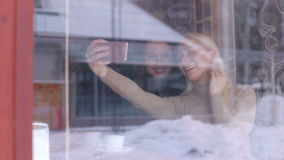 Two girlfriends doing selfie. View from the street through the window. Two girlfriends doing selfie on phone sitting in cafe. View from the street through the stock footage