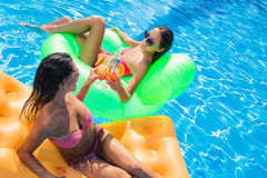 Two girlfriends drinking cocktails in swimming pool Royalty Free Stock Photography