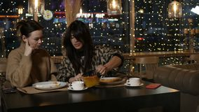Two girlfriends are drinking tea. In cafe stock footage