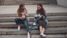 Two girlfriends eating hamburgers outdoors. Girls eating fast food sitting on steps in city stock footage