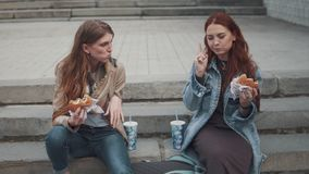 Two girlfriends eating hamburgers outdoors. 20s. Girls eating fast food sitting on steps in city stock video footage