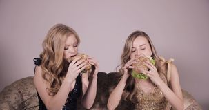 Two girlfriends eating hamburgers. Two women eating very tasty burgers