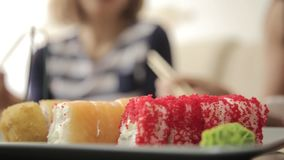 Two girlfriends eating rolls with chopsticks during dinner at the restaurant. close-up Japanese cuisine.  stock video
