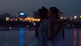 Two girlfriends embrace on a background of a night city. slow motion. Two beautiful girlfriends embrace on a background of a night city. slow motion stock footage