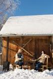 Two girlfriends enjoy tea snow winter cottage stock image