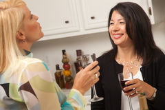 Two Girlfriends Enjoy Wine in the Kitchen Royalty Free Stock Photos