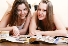 Two girlfriends with fashion magazines Stock Images