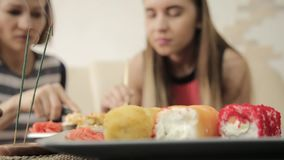 Two girlfriends feed each other during dinner at the restaurant, eating rolls with chopsticks.  stock video footage