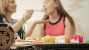 Two girlfriends feed each other during dinner at the restaurant, eating rolls with chopsticks.  stock footage
