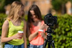 Two girlfriends girl bloggers. Summer nature. Writes the video to the camera. Free space for text. Blurred background. stock photos