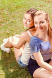 Two girlfriends on grass in park Royalty Free Stock Photo