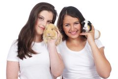 Two girlfriends with guinea pig Stock Photos