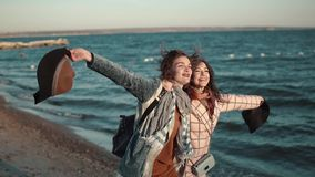Two girlfriends happily run around and frolic in the open air. young woman in autumn coat and hat on the beach at sunset stock video footage