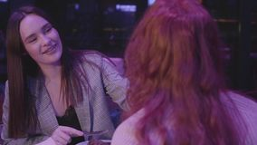 Two girlfriends have dinner in a modern restaurant together. Brunette lady feeding her red-haired girlfriend and smiling. Two girlfriends have dinner in modern stock video