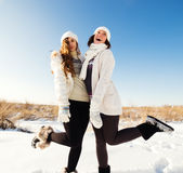 Two girlfriends have fun and enjoy fresh snow Stock Photography