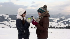 Two girlfriends have tea in mountains stock video footage