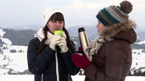 Two girlfriends have tea in mountains stock footage