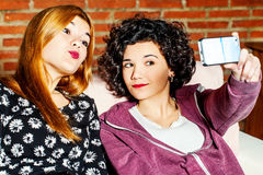 Two girlfriends having fun with camera. Royalty Free Stock Photography
