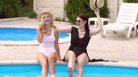 Two girlfriends having fun and spray water in pool. Two happy sexy girls having fun and splashing water relaxing in the pool. Two girlfriends splashing around stock video