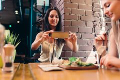 Two girlfriends having healthy lunch in cafe. Young woman taking picture of food with smartphone posting on social media. Two girlfriends having healthy lunch in Royalty Free Stock Photo