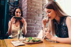 Two girlfriends having healthy lunch in cafe. Young woman taking picture of food with smartphone posting on social media Royalty Free Stock Photography