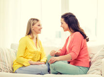 Two girlfriends having a talk at home Stock Images