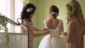 Two girlfriends help dress the bride. Everyone is smiling, the girls are decorated with flowers. The bride is standing with her back to the camera the stock footage