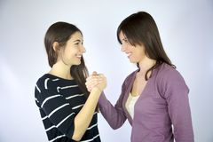 Two girlfriends holding hands smiling laughing Stock Photos