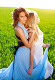 Two girlfriends in long dresses, together outdoors Royalty Free Stock Images