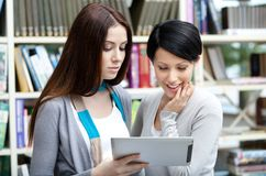 Two girlfriends look at the tablet Stock Images