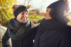 Two girlfriends looking at each other and smiling Stock Photo