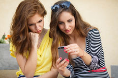 Two girlfriends looking photos on mobile phone Royalty Free Stock Photos