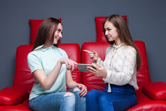 Two girlfriends looking at pictures on phone Stock Photography