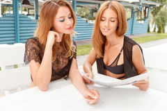 Two girlfriends looking through price list. Choosing cocktail. Two pretty young girlfriends sitting in cafe and looking through price list stock image