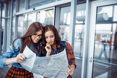 Two girlfriends looking for a route map.Art processing and retou Stock Image