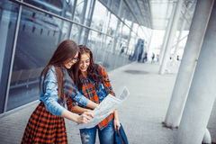 Two girlfriends looking for a route map.Art processing and retou. Ching photos special Stock Images