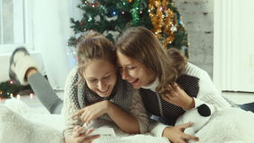 Two girlfriends looking at a smartphone and laughing. On the background of Christmas tree stock footage