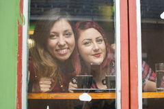Two girlfriends looking through the window Royalty Free Stock Photo