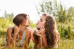 Two girlfriends lying down on grass Royalty Free Stock Photography