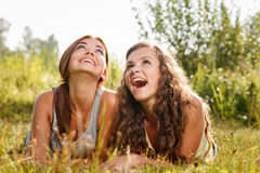 Two girlfriends lying down on grass Stock Images