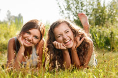 Two girlfriends lying down on grass Royalty Free Stock Images