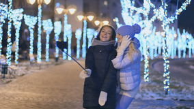 Two girlfriends makes a selfie in winter park at night stock footage