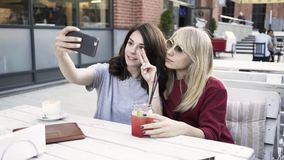 Two girlfriends making a selfie in an outdoors cafe. Two girlfriends are sitting in an outdoors cafe on a summer day and making a selfie with their smartphone stock video footage