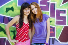 Two Girlfriends Near Graffiti Wall. Royalty Free Stock Photos