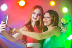 Two girlfriends in a nightclub under the spotlight stock photo